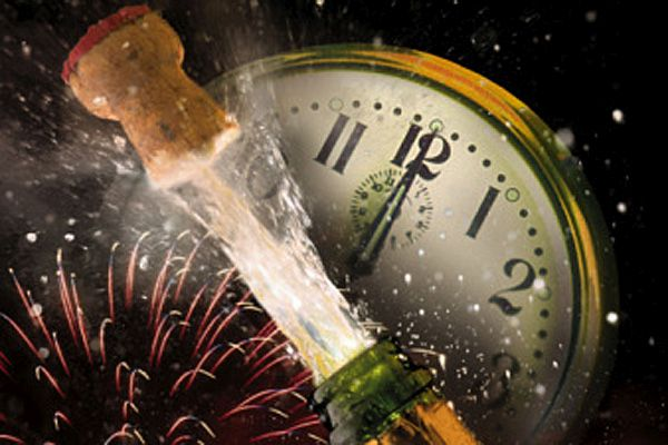 Champagne bottle popping cork at midnight with fireworks